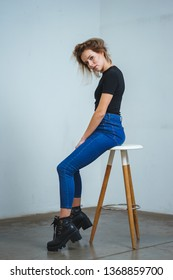 Model tests. Photo session model in studio. Simple attractive portraits for a young beautiful girl in an empty room. Snaps. Attractive girl in jeans,  black shirt. Cheerful girl sitting on a bar stool
