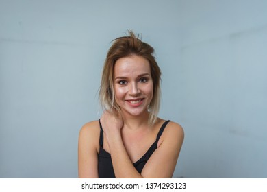 Model tests. Photo session model in studio. Simple attractive portraits for a young beautiful girl in an empty room. Snaps. Attractive girl in jeans,  black shirt. Closeup cheerful girl headshot