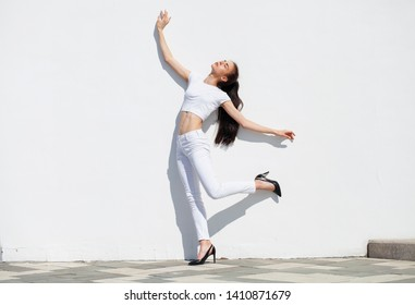 Model tests. Young beautiful brunette girl posing against a white wall in bright sunny weather