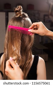 model with a topknot having her hair being brushed by a professional hairdresser using a pink brush in a beauty salon. concept of carefull hair treating