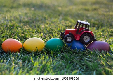 model of a toy red tractor, eggs painted in rainbow colors lie on the grass. Business concept of Easter greetings for farms. postcard. copy space