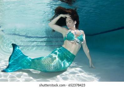 Model underwater in a pool wearing a green  mermaids tail.