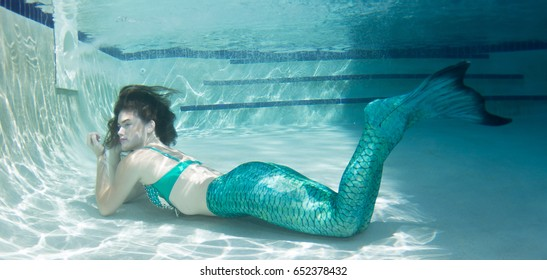 Model underwater in a pool wearing a green  mermaids tail.
