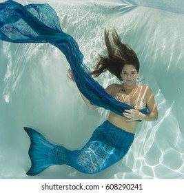Model underwater swimming with a mermaid tale.