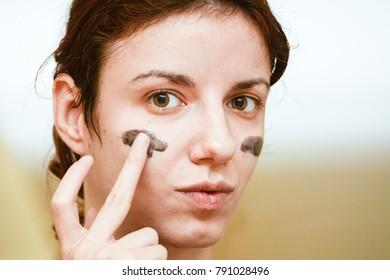 Model using a dark skin exfoliating mask with coal