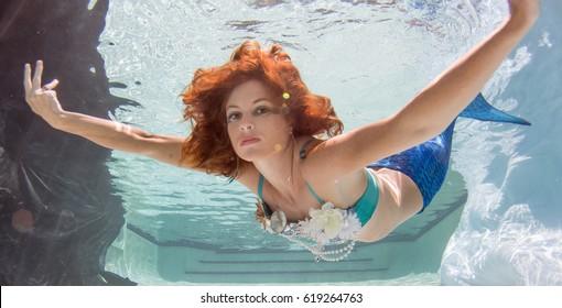 Model using a mermaid's tail underwater.