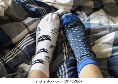Model using a pair of mismatched socks in the bed