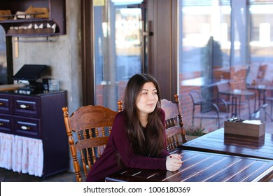 Model waiting photographer for photoshoot in cafe, Asian smiling girl sitting near wooden table. Young woman with long hair and neat red manicure wearing dress looking around. Concept of photosession