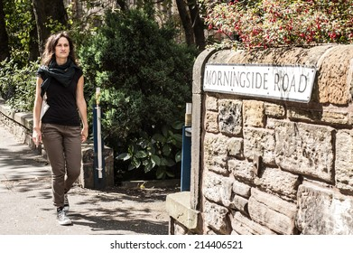 Model walking in a street in Morningside next to a wall with a roadsign.  Morningside road, Edinburgh, UK.