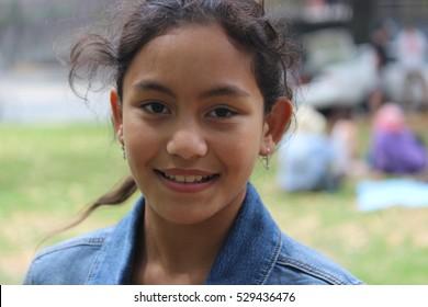 Model wearing a denim jacket smiles at a park.
