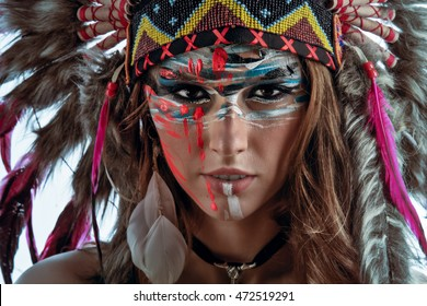A model wearing Native American hat feather roach. Beautiful face with wild creative colorful makeup.  Indigenous peoples of the Americas outfit. Closeup portrait. Ethnic woman with feathers on head