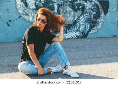 Model wearing plain black t-shirt, boyfriend jeans, sneakers and hipster sunglasses posing against street wall, teen urban clothing style, mockup for tshirt print store