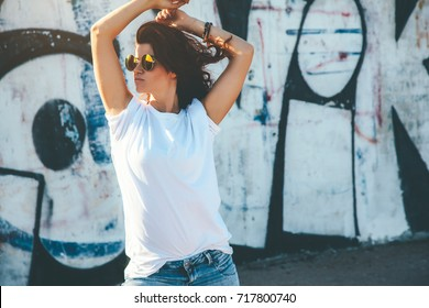 Model wearing plain white tshirt and hipster sunglasses posing against street wall, teen urban clothing style