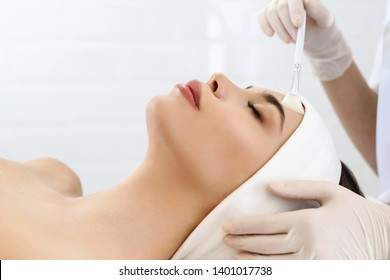 Model in white headband bandage cap lying on couch with closed eyes. Hand of beautician doctor in white glove touching her face with brush. Head and shoulders, healthcare, cosmetology, beauty clinic