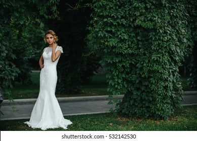 Model in a white maxi dress stands behind a pass in the park