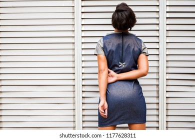 Model of women's fashion poses in rear view in front of a white lattice with summer clothes.