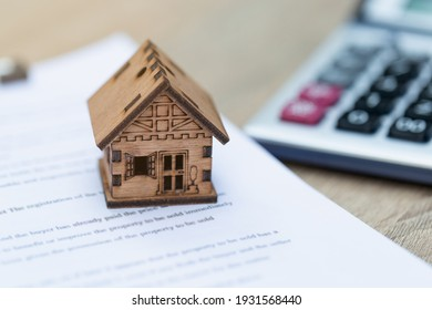 A model wooden house placed on the house purchase contract Real estate ideas, buying a home, landlord, renting a mortgage, buy a home for the future.