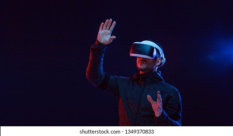 Model young man with beard in glasses of virtual reality on dark background.. Augmented reality, science, future technology concept. VR. Futuristic 3d glasses with virtual projection. Neon light.