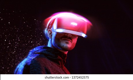 Model young man with beard in glasses of virtual reality on dark background. Augmented reality, future technology concept. VR. Neon light.