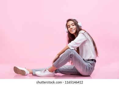Model young trendy beautiful girl with natural make-up with headphones on a pink background fashion Studio shot
