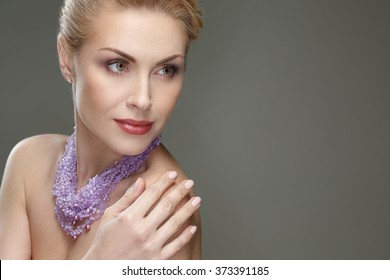 Modeling master. Horizontal portrait of a beautiful mature woman wearing necklace looking away smiling touching her shoulder copyspace on the side