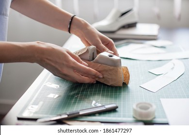 Modelling design of a shoes. Workplace of shoe designer. Hands of designer draw a shoe design on a new shoes at his workshop.