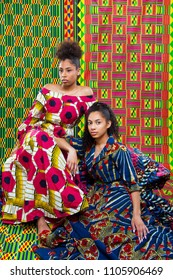 Models wearing west african fashion clothes with a west african fabric backdrop
