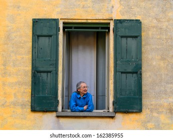 MODENA, ITALY - APRIL 7, 2013 - An old woman looks out of her window in Castelfranco Emilia, Modena. Italy has one of the highest life expectancy rate in the world.