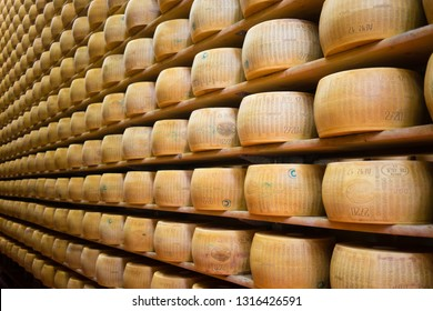 Modena, Italy - February, 2019: Parmigiano Reggiano (Parmesan Cheese) on the racks of a maturing storehouse in diary farm in Modena