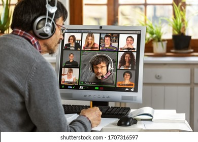 A moderator manages a video conference from his home office