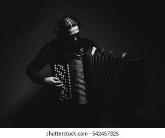 Modern accordion player with Serbian money on an instrument, in black and white.