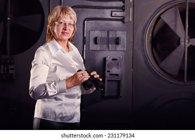 Modern adult business woman looking through binoculars. Woman in business attire holding a pair of binoculars. Watch with binoculars in search of something. Concept screen saver or insurance company.