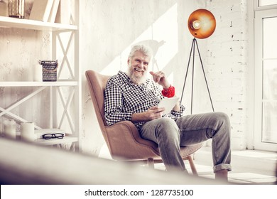 Modern adulthood. Cheerful gray-haired male person keeping smile on his face while sitting in the middle of room