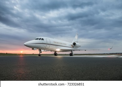 Modern advanced private business jet ready to take off with sunrise in the background and  clouds above airplane