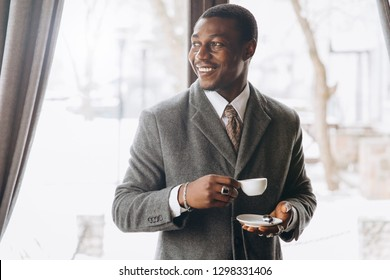 Modern african american businessman drinking cup of coffee in restaurant.