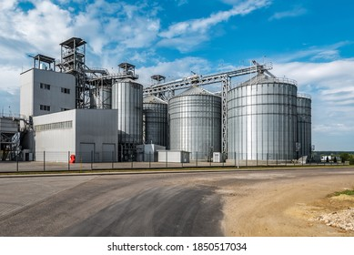 Modern agricultural silos or grain elevator with blue sky on the background. Storage of grain and other different cereals. Sunflower oil factory