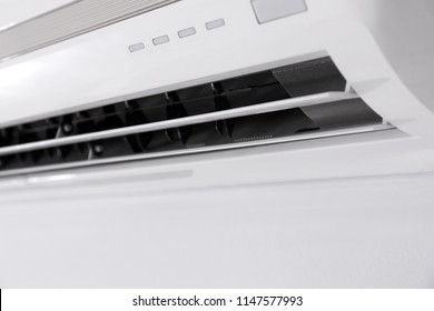 Modern air conditioner on white wall indoors, closeup view
