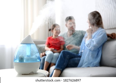 Modern air humidifier and blurred family on background