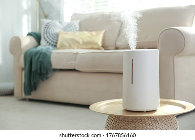 Modern air humidifier on table in living room. Space for text