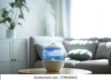 Modern air humidifier on table in living room