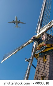 modern airplane flies past a traditional dutch windmill
