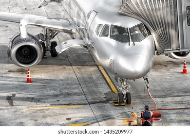 modern airplane on runway at airport preparing for departure aerial closeup front view of passenger aircraft parked to terminal gate with pilot in cockpit and technical maintenance staff on tarmac