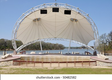 Modern amphitheater stage beside river at city park.