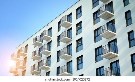 Modern apartment building on a sunny day with a blue sky. Facade of a modern apartment building.Glass surface with sunlight. Rising sun on the horizon.