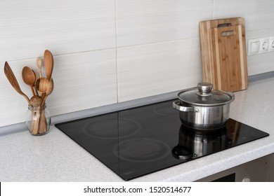 Modern apartment with contemporary interior, built in kitchen appliance and white tile on wall with copy space. Black ceramic induction stove with saucepan, wooden cutlery and cutting board