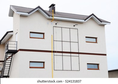 Modern apartment house with chimney on the metal roofing.