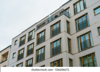modern apartment house with white facade and brown wooden windows