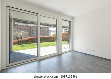 Modern apartment with large, bright windows. View on a green garden