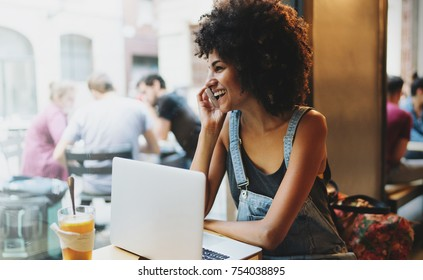 Modern architect female glad to receive a mobile phone call from a client who approved the project. Hipster girl chatting with friend by a smartphone while sitting in a coffee shop with a laptop.