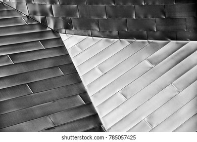 Modern architectural abstract of shiny metal panels reflecting light that highlight a triangle section.